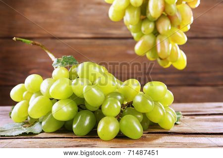 Bunches of ripe grapes on wooden table on wooden wall background