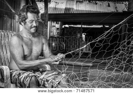 Thai fishermen mending his fishing net