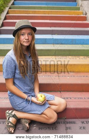 Young pretty girl sitting on the multicolored stone steps, outdoors.