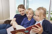 stock photo of storybook  - Father and children reading storybook on sofa at home - JPG