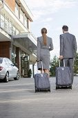 stock photo of carry-on luggage  - Back view of businesspeople walking with luggage outside hotel - JPG