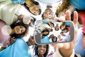 stock photo of huddle  - Hand holding smartphone showing friends forming huddle - JPG