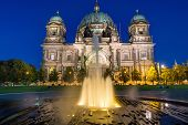 stock photo of dom  - The Berlin Dom and a waterspout fountain at dawn - JPG