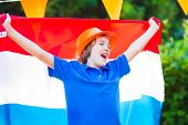 picture of holland flag  - Happy Dutch boy football fan cheering and supporting soccer team of Netherlands during championship celebrating sports victory screaming Hup Holland with national flag - JPG