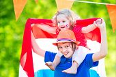 stock photo of holland flag  - Two Dutch children teenager boy and funny little girl celebrating national holiday of Netherlands playing in a garden decorated with Holland and Oranje flags - JPG