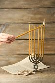 picture of menorah  - Hand burning candles on Menorah on wooden background - JPG