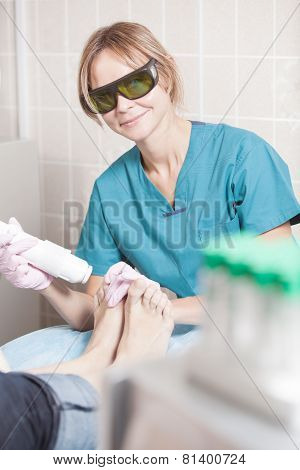 Smiling cosmetician working with laser to treat feet