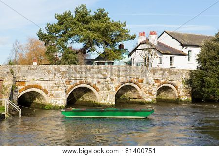 River Avon Christchurch Dorset England UK with bridge and green boat