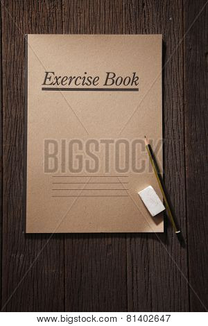 exercise book with pencil and eraser on the wooden background