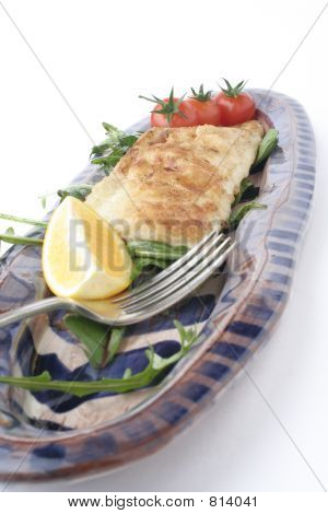 fish snack on ceramic platter; close, low angle