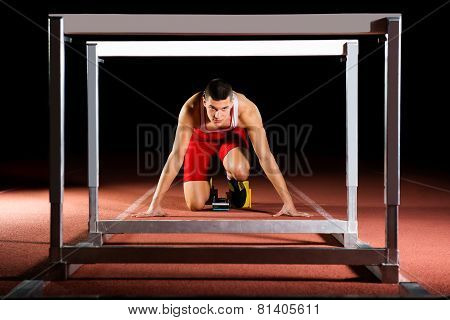 Athlete On The Starting Blocks With Hurdles