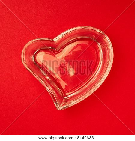 Heart made of glass on the red surface