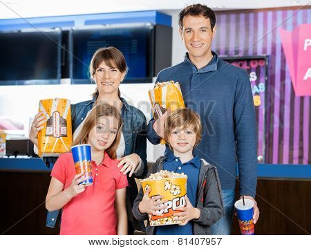 Portrait of happy family holding popcorns and drinks at cinema