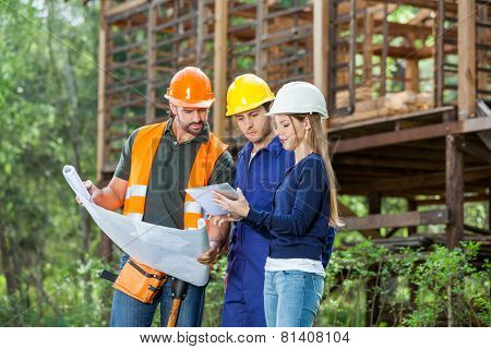 Male and female architects using digital tablet while reviewing blueprint at construction site