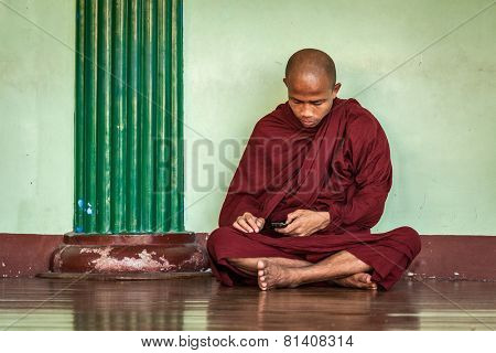 YANGON, MYANMAR - JANUARY 3, 2014: Buddhist monk with phone in Shwedagon Paya pagoda. Yangon, Myanmar