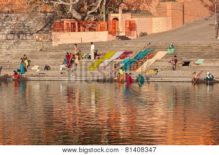 UJJAIN, INDIA - APRIL 25, 2011: People bathing and washing clothes in the morning on ghats of holy Kshipra river. Shipra is one of the sacred rivers in Hinduism