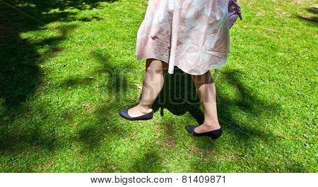 Leg Of Beautiful Girl Walking On The Green