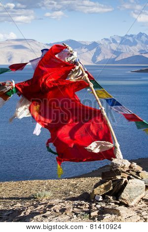 Buddhist Prayer Flags On The Wind Against Blue Lake, Mountai