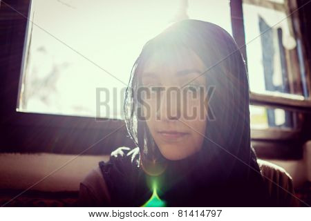 Beautiful asian girl by the window (with harsh direct sun in background)