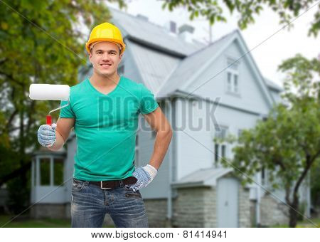 repair, construction, people, building and maintenance concept - smiling male manual worker in protective helmet holding paiting roller over house background