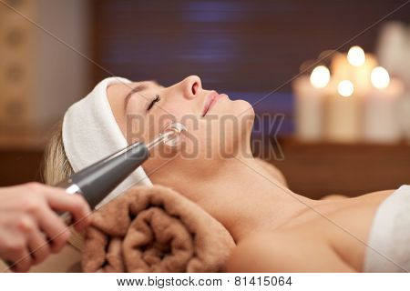 people, beauty, spa, cosmetology and technology concept - close up of beautiful young woman lying with closed eyes having face massage by massager in spa
