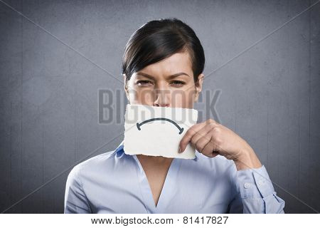 Unhappy young businesswoman holding empty white card with space for text in front of her mouth, isolated on grey background.