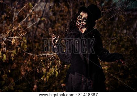 Scary zombie girl standing outdoor. Sugar skull. Halloween.