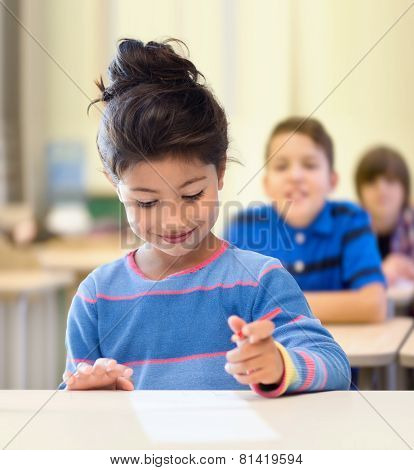education, elementary school and children concept - happy little student girl with pen and paper writing over classroom and classmates background