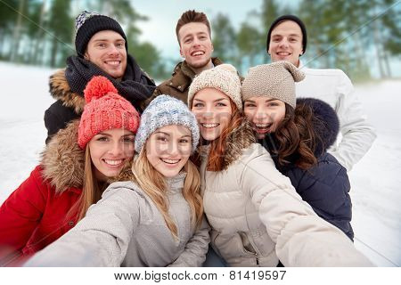 winter, technology, friendship and people concept - group of smiling men and women taking selfie outdoors