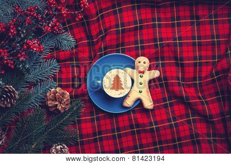 Cappuccino With Gingerbread Man And Pine Branch On Tartan Background