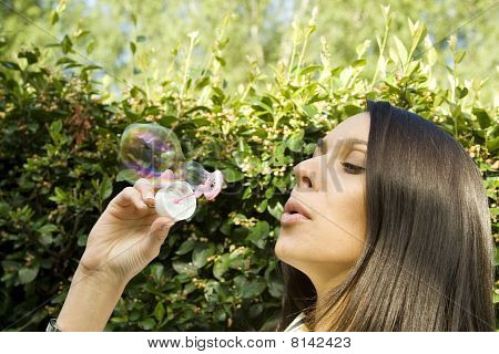 Young woman blowing bubbles in green park