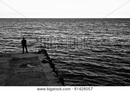 Evening. Jetty. Fisherman
