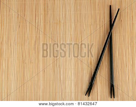 Pair of chopsticks on light bamboo mat background