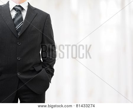 Businessman In Black Suit With Hand In Pocket With Blurred Background