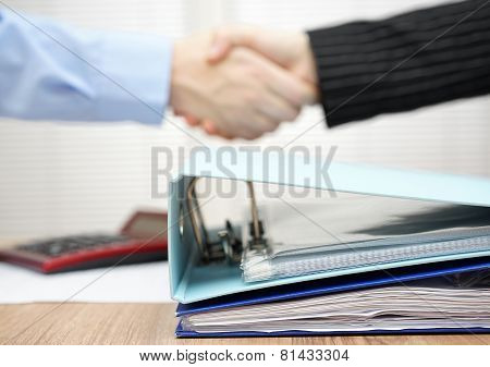 A Lot Of Documentation In Binder With  Handshake In Blur