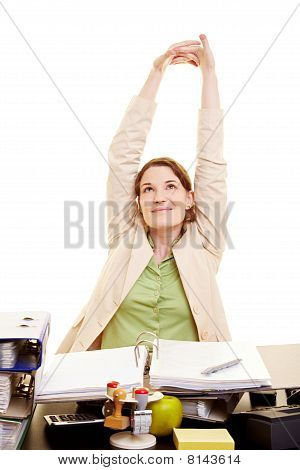 Businesswoman Stretching At Her Desk