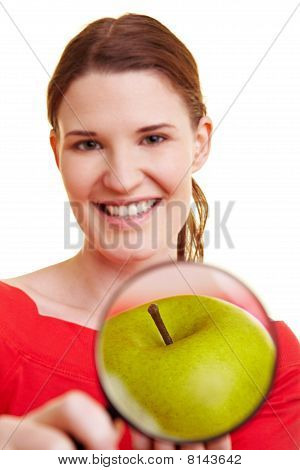 Woman Holding Magnifying Glass In Front Of Apple