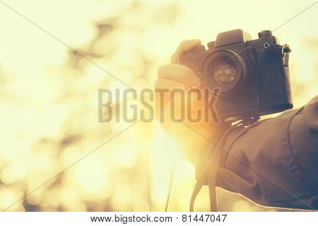 Man hand holding retro photo camera outdoor hipster Lifestyle