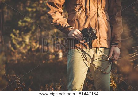 Young Man with retro photo camera outdoor hipster Lifestyle forest nature on background