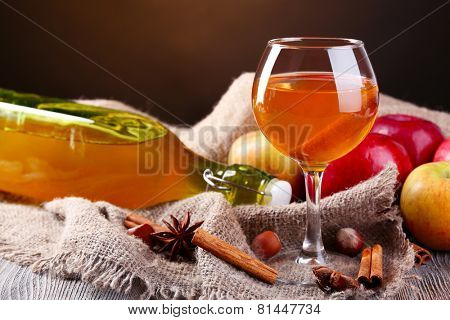 Apple cider in wine glass and bottle, with cinnamon sticks and fresh apples  on table, on dark background
