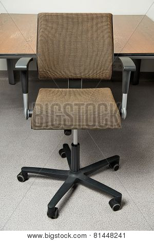 Stylish Brown Office Chair In Front Of A Wooden Meeting Desk
