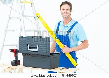Portrait of happy carpenter holding spirit level at table over white background
