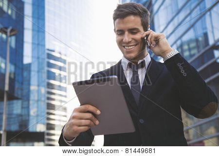 Businessman using a mobile phone and digital tablet
