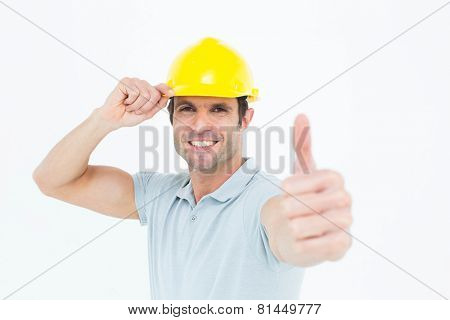 Portrait of architect wearing hardhat while showing thumbs up sign over white background