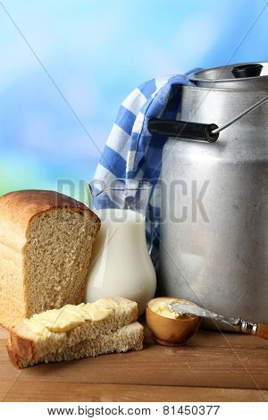 Retro can for milk with fresh bread and jug of milk on wooden table, on bright background. Bio products concept