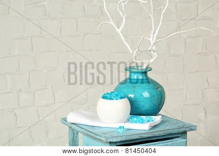 Interior with decorative vases on nightstand and white brick wall background
