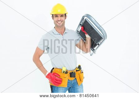 Portrait of confident worker carrying step ladder over white background