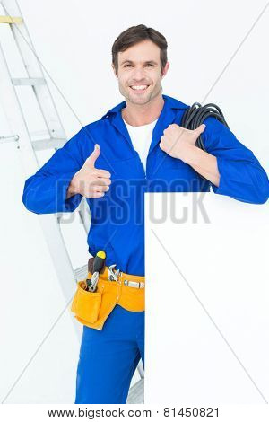 Portrait of electrician with wire and bill board gesturing thumbs up over white background