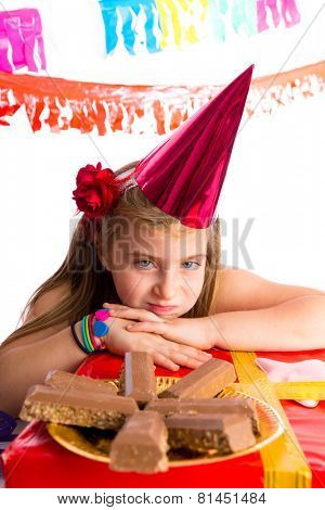Bored gesture blond kid girl in party with chocolates and birthday hat