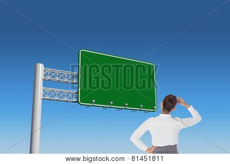 Businesswoman scratching her head against blue sky